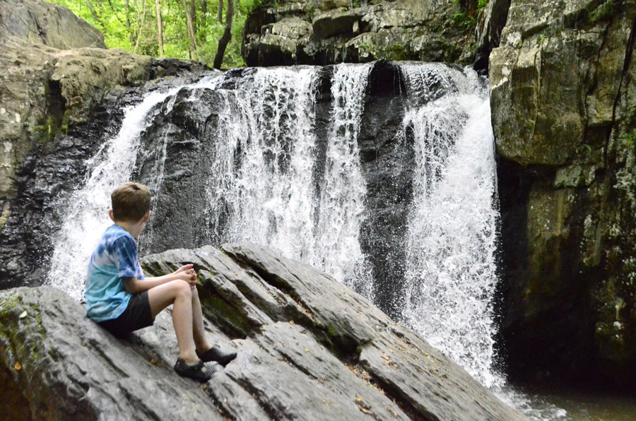 child looking at waterfall
